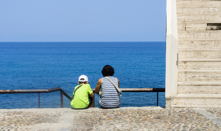 Mom and son sitting in front of the sea