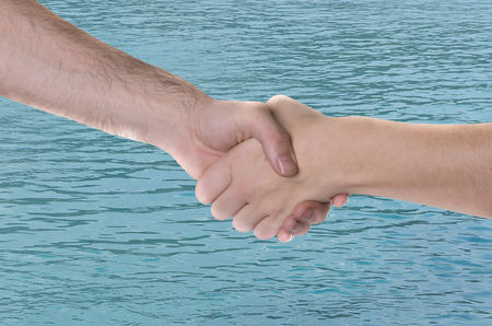 Shaking on an agreement over the water Stock Photo
