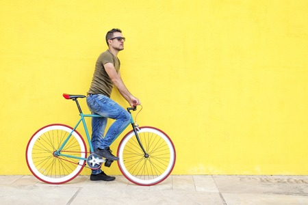 Side view of a young trendy man with a fixed bike wearing casual clothes while looking away against a yellow wall outdoors in a sunny day