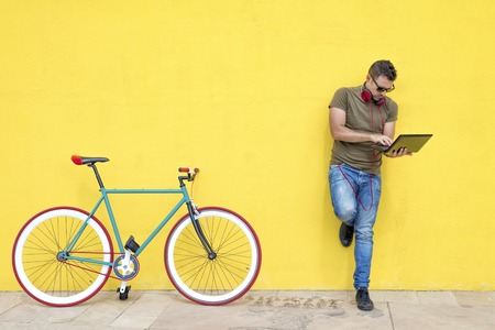 Front view of a young trendy man with a fixed bike wearing casual clothes while using a laptop standing against a yellow wall outdoors in a sunny day