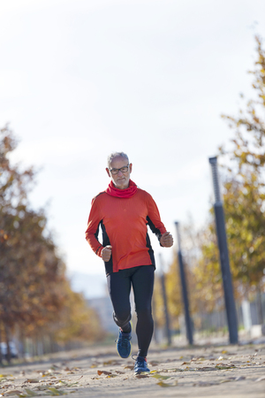 Front view of senior man in sport clothes jogging in a city park in a sunny day
