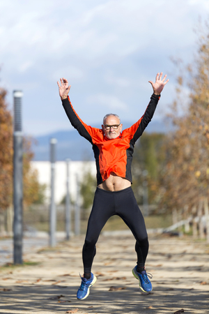 One senior runner man jumping arms up after running