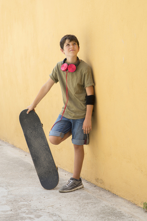 Young boy leaning on yellow wall with headphones on neck, holding a skateboard while looking away in a bright day