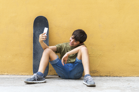 Front view of a young boy sitting on ground leaning on a yellow wall while using a mobile phone to take a selfie