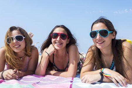 sorridenti belle ragazze migliori amiche sdraiate sulla spiaggia mentre guardano la fotocamera. Archivio Fotografico