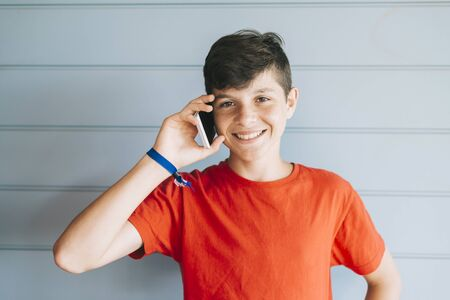Young teen with red t-shirt standing against wall while using phone