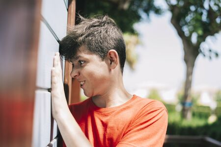 Side view of teenage male grimacing against a outdoors wall