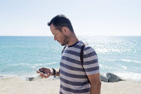 Side view of a young man in t-shirt while using mobile phone on seashore in sunny day