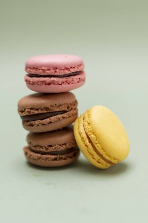 Colored tasty  macaroons over a green background. 写真素材