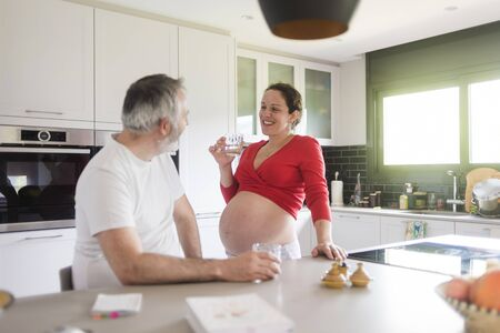 Portrait of smiling laughing white Caucasian couple two people, pregnant woman with husband in the kitchen, lifestyle healthy pregnancy happy life concept