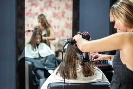 Woman having hair stylized with drier Banque d'images