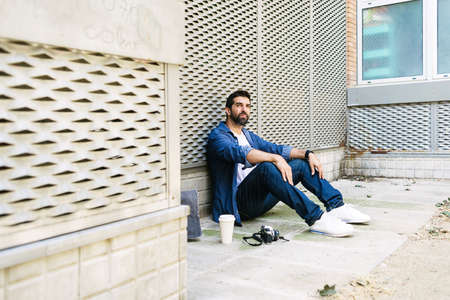 Cheerful bearded man in casual attire sitting on street ground while relaxing on a coffee break