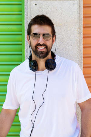 Portrait of a beaded guy with sunglasses and headphones on neck while looking camera