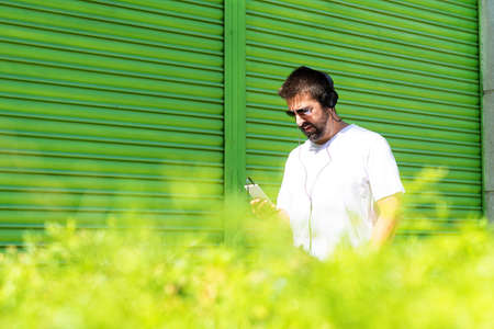 Bearded guy with headphones and sunglasses using a smartphone while listening music