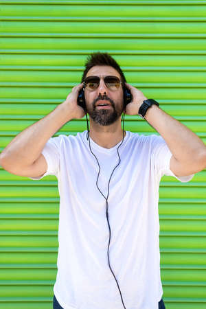 Cool trendy funny beard guy in headphones listening music on colored background. Banque d'images