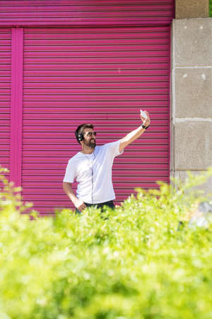 Bearded guy with sunglasses taking a selfie against pink wall