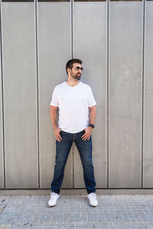 Bearded guy in sunglasses leaning on metallic wall with hands on pocket while looking away