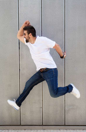 Bearded guy with sunglasses jumping against metallic wall Stock fotó