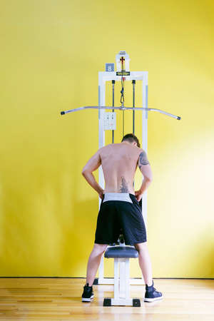 Fit man on lat pull down machine at the health club. Work out on Pull down Weight Machine Imagens