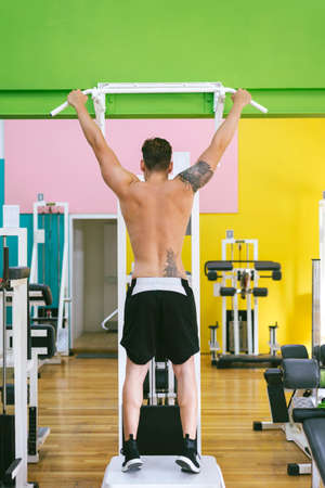 Muscular man workout doing pull ups on bar in gym,Man working out in a fitness club. Imagens