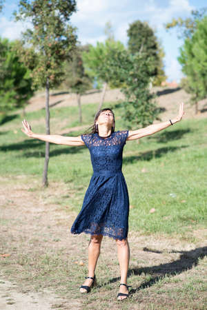 Happy hispanic woman in blue dress and arms raised standing in a public city park