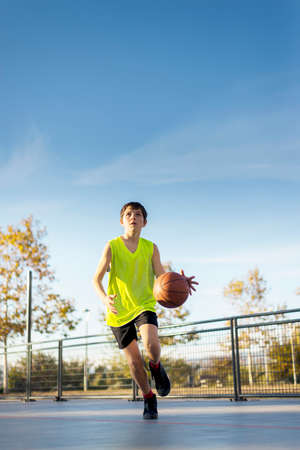 Cute boy in yellow shirt plays basketball on city playground. Active teen enjoying outdoor game with orange ball. Reklamní fotografie