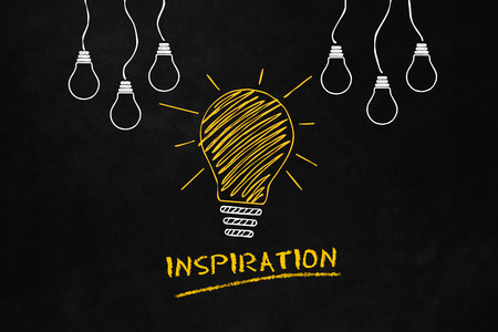 An inspiration metaphor with a Lightbulb on a blackboard, A conceptual design of a inspirational idea, A Big Yellow Light Bulb with 6 smaller white light bulbs and Text Inspiration
