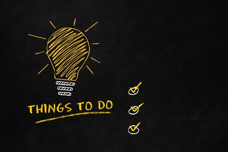 things to do: Things to do concept with a Lightbulb on a blackboard, A big yellow bulb with 6 smaller lightbulbs and text Things to do, Conceptual symbol for to do list Stock Photo