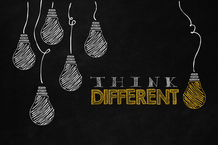 enterprising: Unique thinking concept isolated on a blackboard with designed light bulbs. A slogan to motivate thinking differently. Philosophy concept about freedom of mind and unconventional thinking. Stock Photo