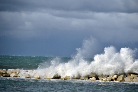 windy day at sea with big waves against rocks Stock Photo