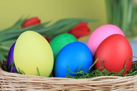 Colorful decorative Easter eggs in wicker basket. photo
