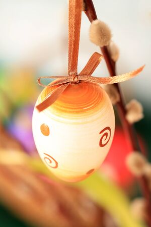 Decorative hand painted Easter egg hanging on branch of plant with colorful background. photo