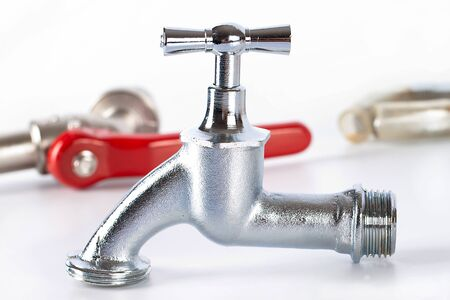 Closeup of modern water tap with plumbing items in background; isolated on white background. Stock Photo