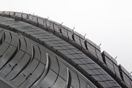 Close-up of a black rubber tire with tread pattern.