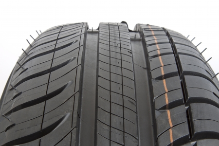 close fitting: Close-up of a black rubber tire with tread pattern.