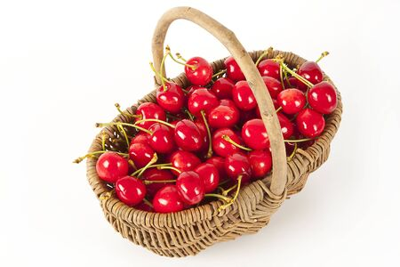 Wicker basket of red cherries; isolated on white background.