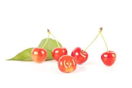 harvests: Five red cherries with green leaves isolated on white studio background.