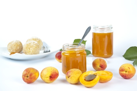 A background of whole apricots and jam or preserves