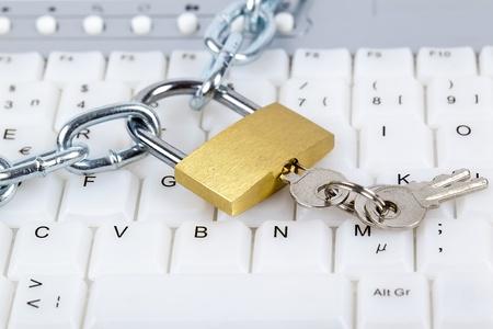 hacking: Tastiera del computer con catena d'argento, lucchetto e chiavi relative alla sicurezza del computer o di controllo parentale per l'accesso a internet.