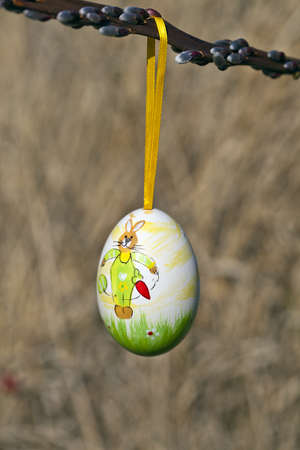 Hanging easter egg on brown background. Stock Photo