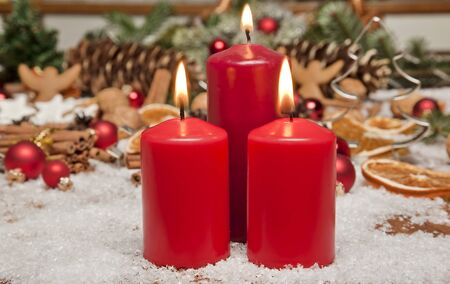 A glowing red candle with christmas decorations