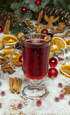 Glasses of red mulled wine on table with cinnamon sticks, Christmas decorations in background