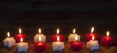 Red candles burning on black background with copy space.