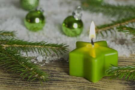 A glowing green candle with christmas decorations