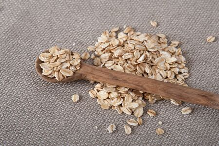 wild oats: Pile of oat on a beige table cloth with a wooden spoon