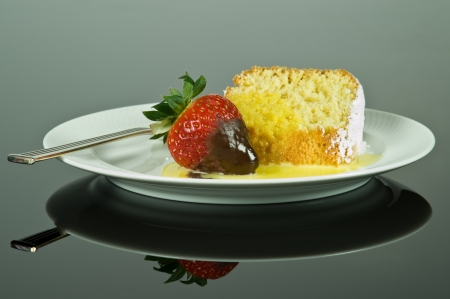 a white plate with cake and strawberry that is reflected on the surface   photo