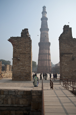 quitab: The Qutab Minar In New Delhi, India  People are visiting the ruins and walking In Front Of The Famous Qutab Minar