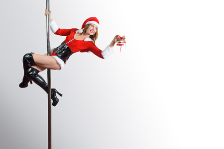 Pole dancer girl as Santas helper decorating something Reklamní fotografie