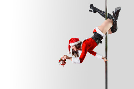 pole dance: Pole dancer girl as Santas helper decorating something Stock Photo