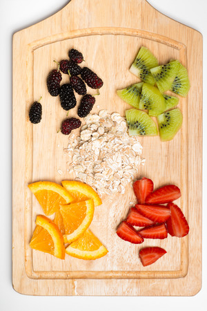 sweet segments: Mix of fruits and berries on wooden cutting board